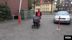 Somali migrant mother Rahma Abukar Ali walks her baby daughter, Sophia, in a stroller at a refugee center in a small German town near Düsseldorf, where she is awaiting a response to her application for asylum, Oct. 2015. (A. Osman/VOA)