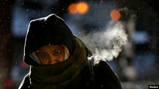 A woman walks in frigid cold temperatures though downtown Chicago, Illinois, Jan. 6, 2014.