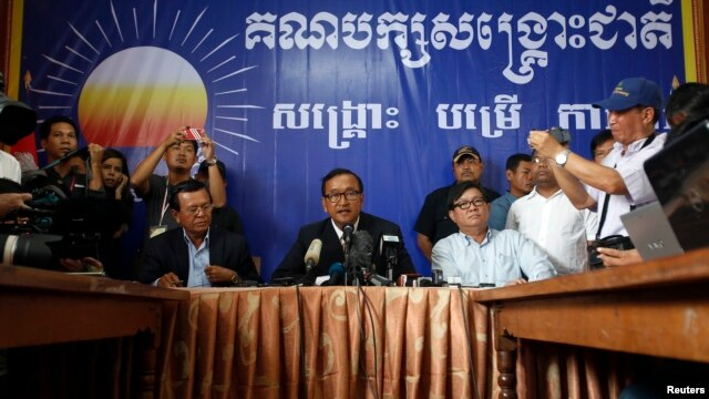 Sam Rainsy (C), president of the Cambodia National Rescue Party (CNRP) addresses reporters at his party's headquarters in Phnom Penh, July 29, 2013.