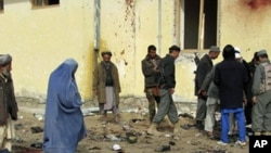 Afghans stand at the site of a suicide attack in Emam Saheb district of Kunduz province February 21, 2011