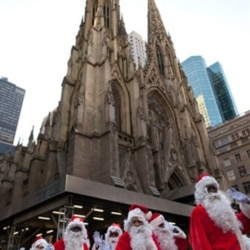 Charity workers dressed as Santa Claus pass St. Patrick's Cathedral in New York City in an annual parade to raise money for a holiday food program for needy residents