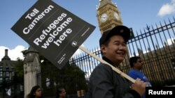 A protester holds up a placard during a demonstration in London to express solidarity with migrants and to demand the government welcome refugees into Britain, Sept. 12, 2015.