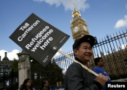 FILE - A protester holds up a placard during a demonstration in London to express solidarity with migrants and to demand the government welcome refugees into Britain, Sept. 12, 2015.