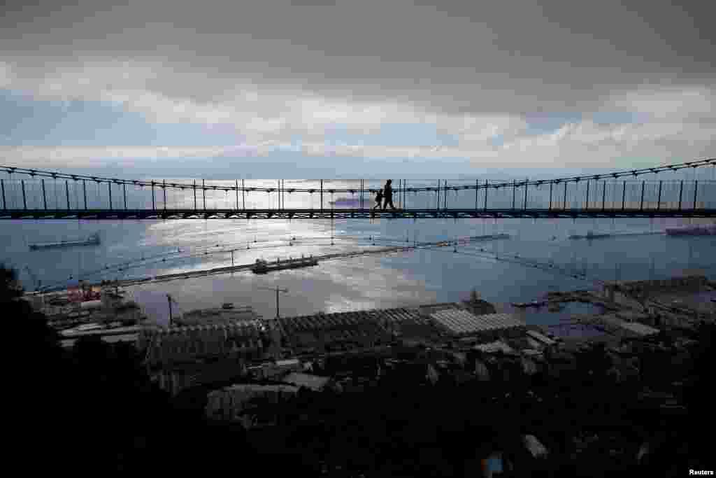 ភ្ញៀវទេសចរដើរកាត់ស្ពាន Windsor Bridge នៅព្រំដែនអង់គ្លេសក្នុងទីក្រុង Gibraltar ដែលទាមទារដោយប្រទេសអេស្ប៉ាញកាលពិថ្ងៃទី១៨ មេសា២០១៨។