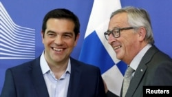 Greek Prime Minister Alexis Tsipras (L) is welcomed by European Commission President Jean-Claude Juncker ahead of a meeting at the EU Commission headquarters in Brussels, June 3, 2015.