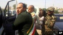 İranın İnqilab Keçikçiləri Ordusunun üzvləri yaralı yoldaşlarını daşıyır