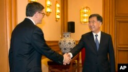 U.S. Treasury Secretary Jacob Lew, left, shakes hands with Chinese Vice Premier Wang Yang as he arrives for a meeting at the Zhongnanhai Leadership Compound in Beijing Monday, March 30, 2015.