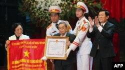 Chủ tịch nước Việt Nam Trương Tấn Sang trao giải thưởng anh hùng lực lượng vũ trang cho Cựu Phó Chủ tịch nước Nguyễn Thị Bình và ông Lưu Văn Lợi, người đại diện nhóm đàm phán từ hai miền Nam Bắc, ở Hà Nội, 25/1/2013