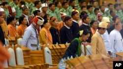 National League for Democracy (NLD) leader Aung San Suu Kyi, center in front row, takes her seat after standing along with other lawmakers for the arrival of Speaker of Union Parliament during the inauguration session of the parliament, Feb. 8, 2016, in Naypyitaw, Myanmar.