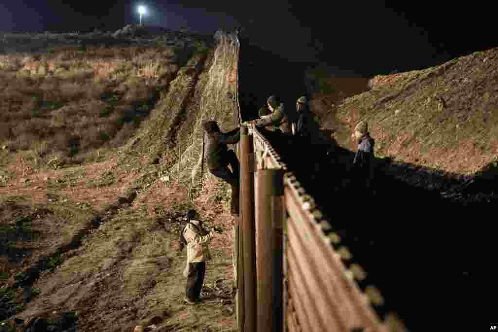 온두라스 출신 이민자들이 멕시코 티후아나와 미국 샌디에이고 사이 장벽을 넘고 있다.