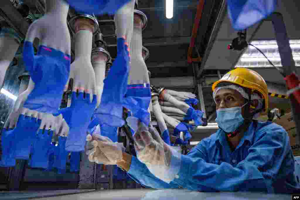 A worker inspects gloves at the Top Glove factory in Shah Alam, in the outer part of Kuala Lumpur, Malaysia.