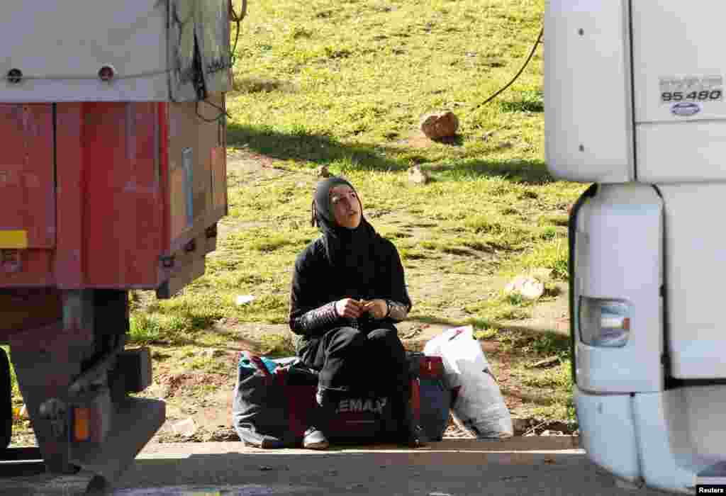 A Syrian woman waits for the opening of Cilvegozu border gate near the town of Reyhanli in Hatay province at the Turkish-Syrian border.