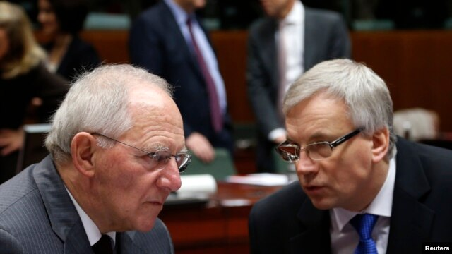 Germany's Finance Minister Wolfgang Schaeuble listens to his Lithuanian counterpart Rimantas Sadzius (R) during a European Union finance ministers meeting in Brussels, Dec. 10, 2013.