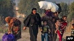 Civiles huyen durante el bombardeo turco en la ciudad de Ras al-Ain, en el noreste de Siria, en la provincia de Hasakeh, a lo largo de la frontera turca, el 9 de octubre de 2019.