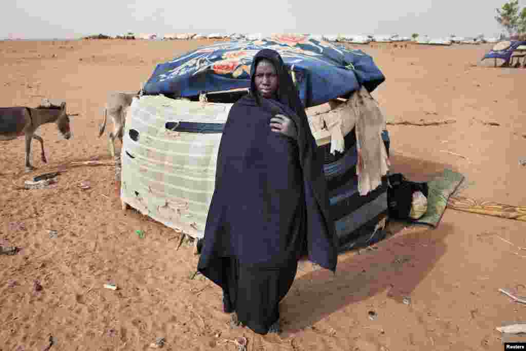 Kadjiatou Mint Sidi, 50, in front of her makeshift shelter at Mbera refugee camp in southern Mauritania. Sidi fled her hometown of Lerneb, Mali, in the beginning of May and rode a donkey-driven cart for six days to arrive at the camp.