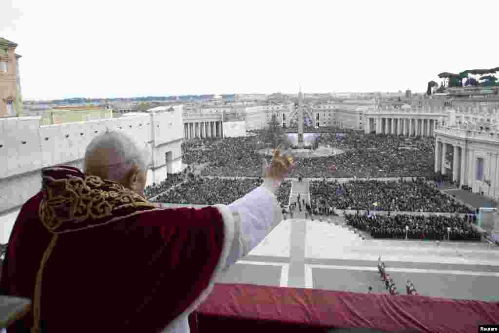 """Папа Бенедикт XVI благословляет толпу с балкона на площади Святого Петра в Ватикане во время своего рождественского обращения """"Городу и миру"""""""