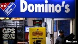 Seorang pekerja sedang mengantar pizza dari sebuah gerai Domino's di Sydney,Australia. (Foto:dok/Reuters)