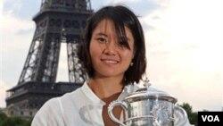 Li Na berpose di depan menara Eiffel setelah menjuarai kejuaraan grand slam Perancis terbuka dengan menundukkan petenis Italia Francesca Schiavone (6/6). Li Na meninggalkan sistim pembinaan olahraga Tiongkok sejak tahun 2008.