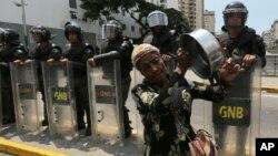 Una mujer suena una cacerola al pasar frente a guardias nacionales bolivarianos en Caracas.