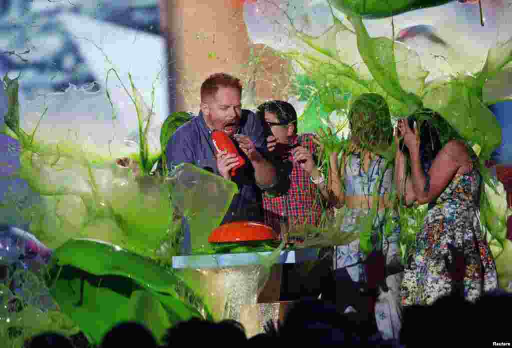 """(L to R) Jesse Tyler Ferguson, Rico Rodriguez, Sarah Hyland and Ariel Winter are slimed while accepting the award for Favorite Family TV Show for """"Modern Family"""" during the 2015 Kids' Choice Awards in Los Angeles, California, March 28, 2015."""