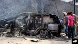 FILE - Yemenis inspect the scene of a car bomb attack that killed a Yemeni senior official in the southern port city of Aden, Yemen, Sunday, Dec. 6, 2015.