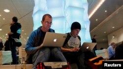 Dua orang pengguna komputer Apple tengah menjelajah internet di jeda waktu kongres komunikasi ke-29 yang diadakan sebuah klub komputer di Hamburg (Foto: dok). Apple menjadi sasaran terbaru peretas komputer bulan ini.