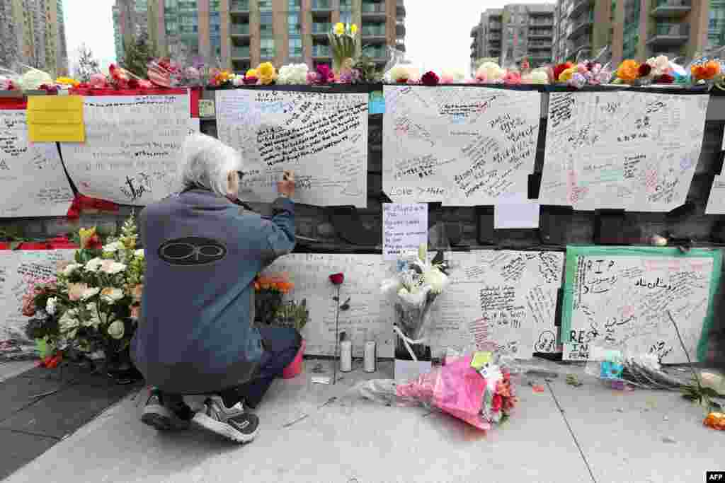 "Jack Young leaves a notes at a makeshift memorial for victims of the van attack in Toronto, Ontario. A van driver suspected of killing 10 people and injuring others when he plowed onto a busy Toronto sidewalk was charged with murder, as Canadian Prime Minister Justin Trudeau urged a rattled nation not to live in fear after the ""senseless attack."""