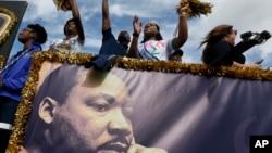 """在迈阿密的一处社区举行的""""马丁·路德·金日""""游行期间,佛罗里达国际大学的花车上的人向观众们挥手。(2017年1月16日)"""