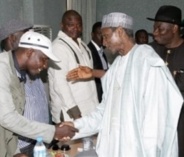 President Yar'Adua (C), flanked by then-Vice President Goodluck Jonathan (R), shakes hands with Government Ekpemupolo (L), commander of rebel group MEND, during their meeting in Abuja on 09 October 2009.