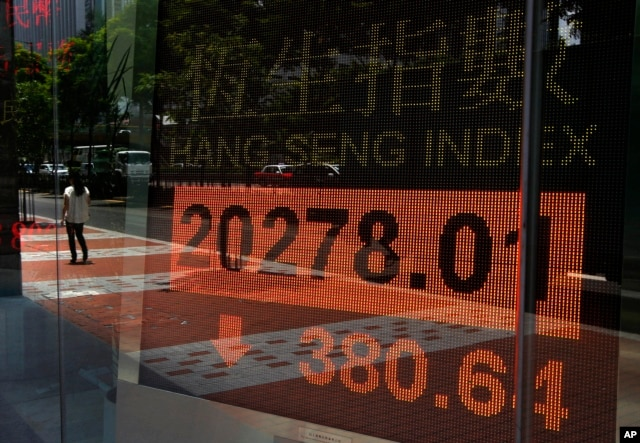 A woman walks past a bank electronic board showing the Hong Kong share index outside a Hong Kong local bank, July 3, 2013.