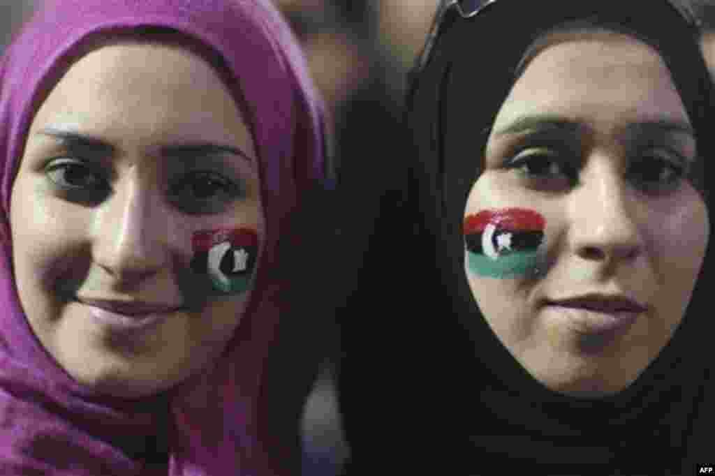Alaa Elshiekh, right, and her sister Yosev Elshiekh, celebrate the revolution against Moammar Gadhafi's regime and ask for more women's rights in Tripoli, Libya, Friday, Sept. 2, 2011. Rebel forces are advancing toward Moammar Gadhafi's hometown Sirte des