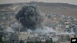 Asap tebal dan puing-puing mengepul akibat serangan udara koalisi yang dipimpin AS di Kobani, Suriah (18/10).