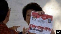 Nhân viên bầu cử hướng dẫn cách bỏ phiếu tại một điểm bầu cử ở Jakarta (ảnh tư liệu, 15/2/2017)