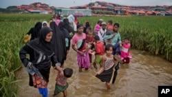 FILE - Rohingya Muslims, who crossed over from Myanmar into Bangladesh, wade past a waterlogged path leading to the Jamtoli refugee camp in Ukhiya, Bangladesh, Nov. 17, 2017.