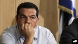 Greek Prime Minister Alexis Tsipras listens during his visit at the transport ministry in Athens, Aug. 12, 2015.