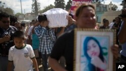 FILE - Relatives carry the coffin containing the remains of 17-year-old Siona Hernandez Garcia, a girl who died in a fire at the Virgin of the Assumption Safe Home, at the Guatemala City's cemetery, March 10, 2017.