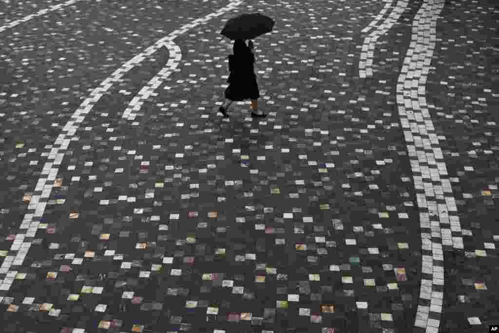 A woman walks with an umbrella during a summer rainfall at Monastiraki square in central Athens, Greece.