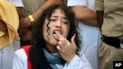 Indian political activist Irom Sharmila licks honey from her hand to break her fast in Imphal, north-eastern Indian state of Manipur, India, Aug. 9, 2016. One of India's most prominent political activists ended a 16-year hunger strike Tuesday.
