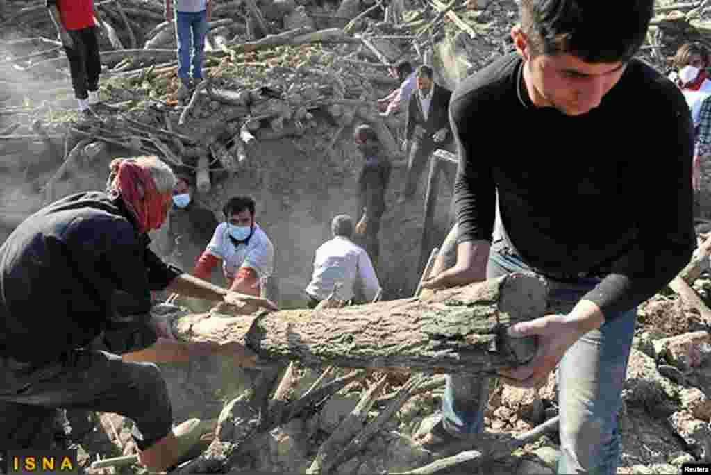 救援人員8月12日在東阿塞拜疆省阿哈爾市附近的阿扎汗村搜尋受害者。伊朗的議員和公眾批評政府救災不力。