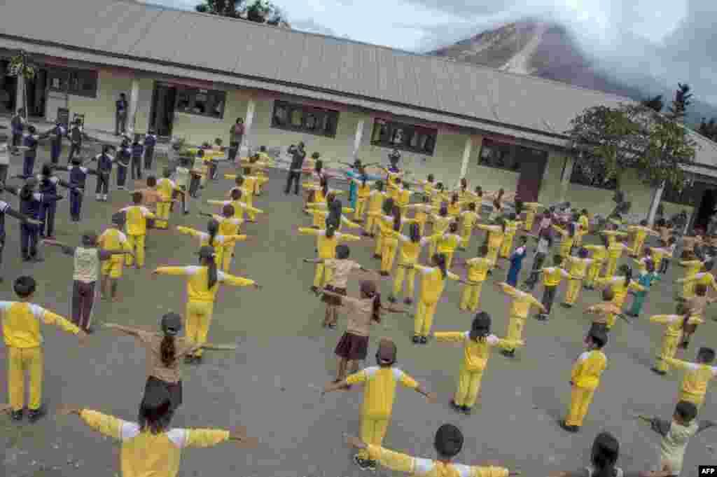 Para murid senam pagi di sekolah sementara Gunung Sinabung memuntahkan abu vulkanik di distrik Karo, Sumatra Utara (12/6). (AFP/SutantaAditya)