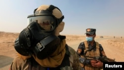 Iraqi forces wear protective masks after winds brought fumes from a nearby sulfur plant set aafire by IS militants, in Qayyara, Iraq, Oct. 22, 2016. Fears are mounting that the jihadist group, in its fight for Mosul, would not hesitate to use chemical weapons.