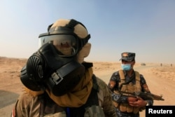 FILE - Iraqi forces wear protective masks after winds brought fumes from a nearby sulfur plant set alight by Islamic State militants, south of Mosul in Qayyara, Iraq, Oct. 22, 2016.