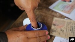Å woman's finger is marked with ink after she cast her ballot in Antananarivo, Madagascar, Oct. 25, 2013.