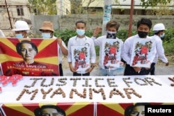 People hold a banner showing the portrait of Aung San Suu Kyi, in Mandalay, Myanmar February 19, 2021 in this picture obtained by REUTERS.