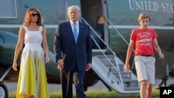 FILE - President Donald Trump, first lady Melania Trump and son Barron Trump walk across the tarmac to board Air Force One at Morristown Municipal Airport, Aug. 20, 2017, in Morristown, N.J.