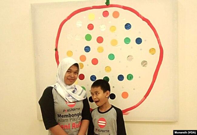 Giyanti bersama putranya Suryo Putro Legowo, kelas 4 SD Luar Biasa, penyandang tuli dan low vision didepan salah satu karya Eksplorasi Titik dengan lingkaran. (foto Munarsih Sahana).