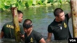 Tentara Thailand memperbaiki pembatas air yang rusak dihantam banjir di Bangkok, Minggu (30/10).