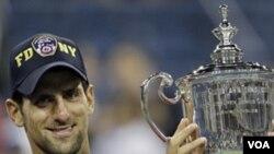 Novak Djokovic memegang trophy setelah menang melawan Rafael Nadal di turnamen grandslam AS Terbuka di New York (12/9).