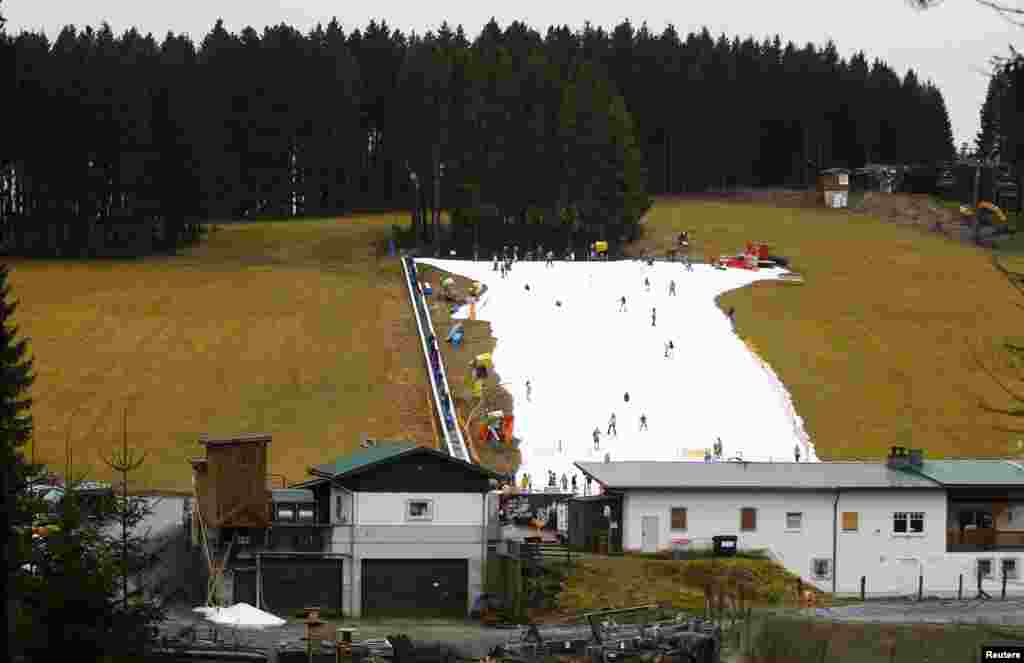 Visitors ski on a piste made with artificial snow on a warm day in the western German ski resort of Winterberg, some 80km southeast of Dortmund.
