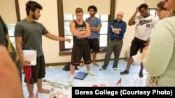 Standing on a map of Asia, Berea College students in a foreign policy class work policy on a crisis exercise. Berea, in Kentucky, offers free tuition to all its students.